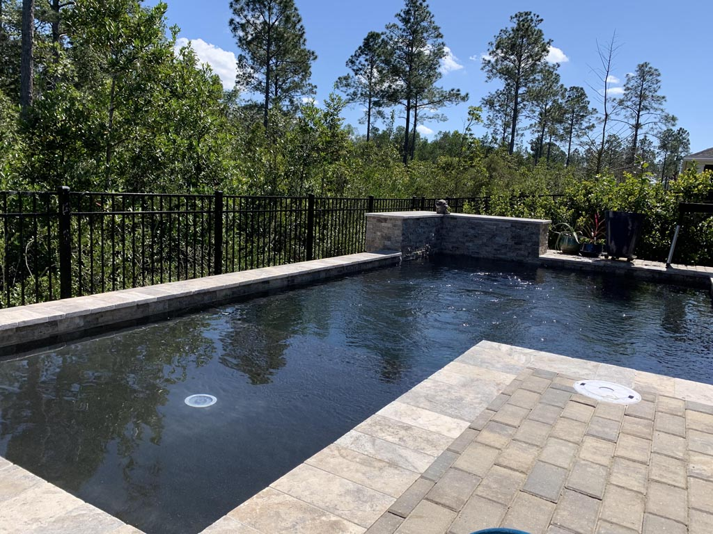 dark color swimming pool with waterfall