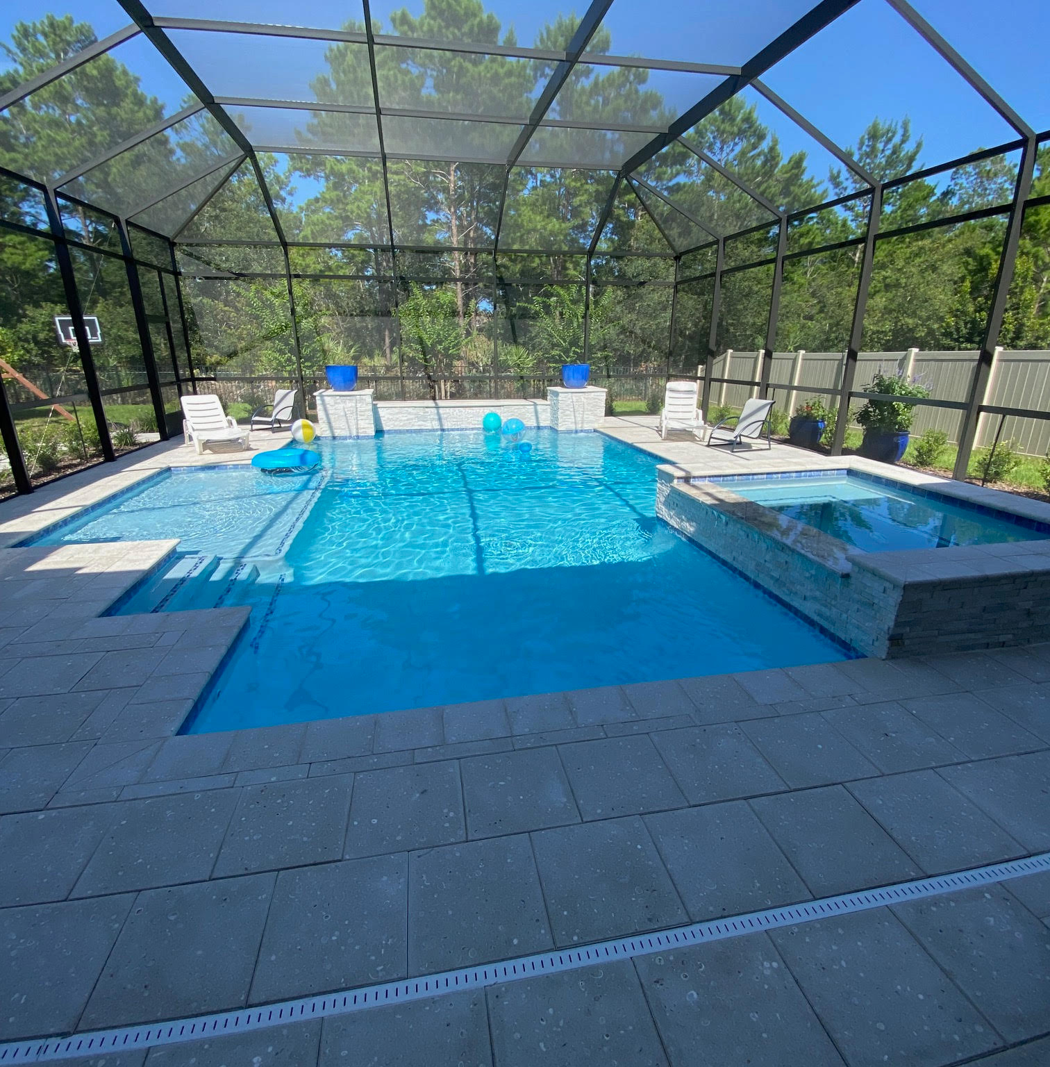 outdoor inground pool and spa combo waterfall screen enclosure